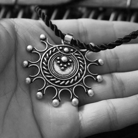 pagan-amulet-sun-necklace-close-up-hand