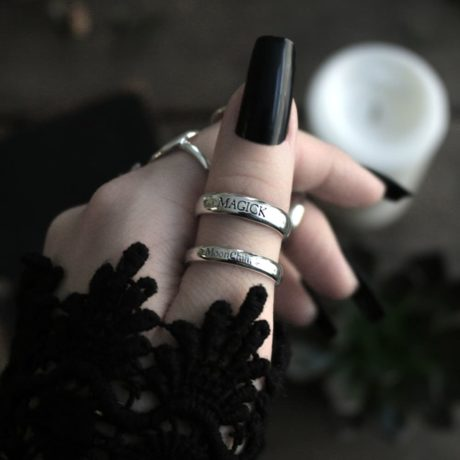 Image with a hand, long black nails and two sterling silver rings, one ring has the text magick and the other ring has the text moonchild.