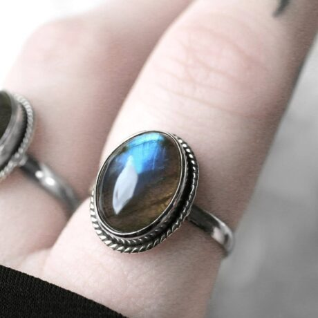Close up photo of a oval turquoise, green and brown labradorite stone ring in sterling silver.