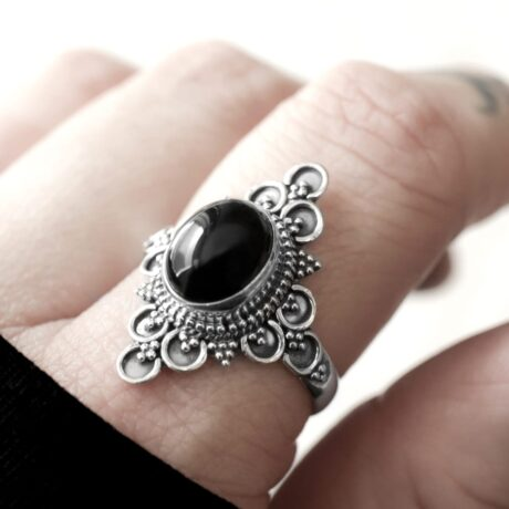 Large sterling silver ring with an oval shaped pitch black onyx crystal.