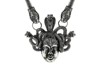 "An antique silver-colored statement necklace with the symbol ""Medusa""."
